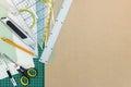 Brown desk with green cutting mat, cutter, ruler, scissors an pe Royalty Free Stock Photo