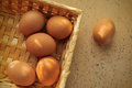 Brown eggs in a basket on textured surface