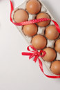 Brown eggs in an egg carton with red polka dot ribbon and bow on white background. Top view. Copy space for text Royalty Free Stock Photo