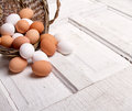 Brown eggs spilling out wicker basket onto antique wooden panel Royalty Free Stock Photo