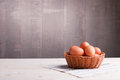 Brown eggs in a wicker basket on a light wooden table and a side Royalty Free Stock Photo
