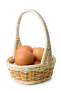 Brown eggs in wicker basket with long handle isolated on white background Stock Image