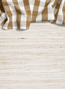 Brown folded tablecloth over oak bleached wooden table Stock Images