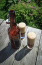 Brown glass bottle and two tall glasses full of frothy dark beer on rustic wooden table in summer garden selective focus Royalty Free Stock Photo