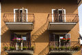 Brown house shutters decorated balconies wall with and with flowers in bardolino a town on the south east shores of lake garda Royalty Free Stock Image