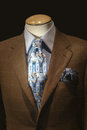 Brown jacket blue patterned tie mannequin in checkered with striped shirt and on a dark background Stock Photo