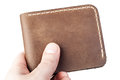 Brown leather wallet in hand isolated on white Royalty Free Stock Photo