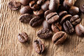 Brown natural coffee grains over wooden table macro close up Stock Photos