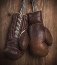 Brown old boxing gloves with a lace over wooden wall Stock Photography