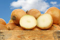 Brown onions and a cut one in wooden crate against blue sky with clouds Royalty Free Stock Photo