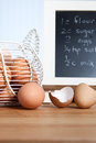 Brown organic eggs with recipe in kitchen a freshly cracked egg a basket full of and a country Royalty Free Stock Photo