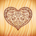 Brown ornate vector heart on wooden background Stock Photo