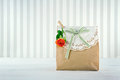 Brown paper gift bag decorated with doily orange rose and green striped ribbon Royalty Free Stock Photography
