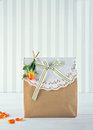 Brown paper gift bag decorated and yellow rose with doily orange green striped ribbon Stock Photos