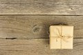 Brown paper wrapped gift box with bow on rustic wood Royalty Free Stock Photo