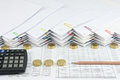 Brown pencil with black calculator between Pile of gold coins Royalty Free Stock Photo