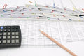 Brown pencil and calculator place on finance account with pile of paperwork as background Royalty Free Stock Photos