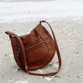 Brown purse on sand Royalty Free Stock Photography