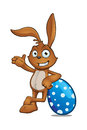 Brown rabbit leaning on blue egg a cartoon character a large easter Royalty Free Stock Photos