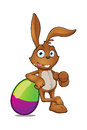 Brown rabbit leaning on purple green egg a cartoon character a large easter Stock Photos