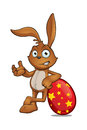 Brown rabbit leaning on red egg a cartoon character a large easter Royalty Free Stock Photography