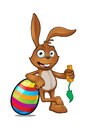 Brown rabbit leaning on a striped coloured egg cartoon character large easter Stock Photo