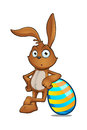 Brown rabbit leaning on a striped egg cartoon character large easter Stock Photo