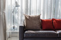 Brown and red pillow on sofa with lamp Royalty Free Stock Photo