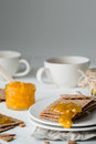 Brown rye crisp bread Swedish crackers with spread orange jam and cups of tea Royalty Free Stock Photo