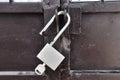 Brown steel door with padlock, unlocked. Royalty Free Stock Photo