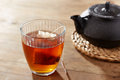 Brown tea on glass cup with black iron maker Stock Image