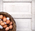Brown white eggs wicker basket antique wooden panel Royalty Free Stock Photo
