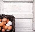 Brown white eggs wicker basket antique wooden panel Royalty Free Stock Images