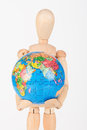 Brown wood mannequin holding concerned a globe protect to Stock Images