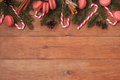 Brown wooden background with branches of spruce, macaroons, and caramel sticks