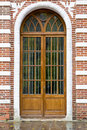 Brown wooden door in brick red and white wall Royalty Free Stock Photo