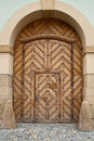 Brown wooden door within door which is a side entrance to a cathedral with a smaller a larger one set in ornate white stone Stock Images