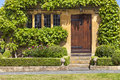 Brown wooden doors to traditional English stoned cottage, garden Royalty Free Stock Photo