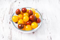 Brown and yellow fresh cherry tomatoes in glass bowl with water drops on wooden table Stock Photography
