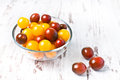 Brown and yellow fresh cherry tomatoes in glass bowl with water drops on wooden table Royalty Free Stock Image