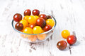 Brown and yellow fresh cherry tomatoes with water drops in bowl a glass on a wooden table Stock Image