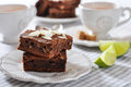 Brownie cake with almond flakes and cup of tea closeup Stock Photo