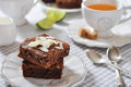 Brownie cake with almond flakes and cup of tea closeup Royalty Free Stock Photography