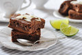 Brownie cake with almond flakes and cup of tea closeup Royalty Free Stock Photos