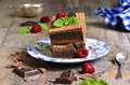 Brownies decorated with raspberry and mint leaf on rustic background Stock Photos