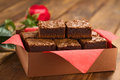 Brownies freshly baked in a brown paper box with red napkin with red rose in the back selective focus focus on the upper left Royalty Free Stock Photography