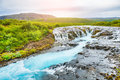 Bruarfoss waterfall with blue water at sunset. Royalty Free Stock Photo