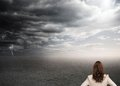 Bruentte businesswoman standing back to camera composite image of under stormy sky Royalty Free Stock Photography