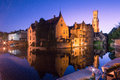 Bruges canal by night a reflects the buildings and belfry of the historic old city of Royalty Free Stock Photos