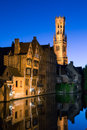 Bruges canal by night a reflects the buildings and belfry of the historic old city of Stock Photo